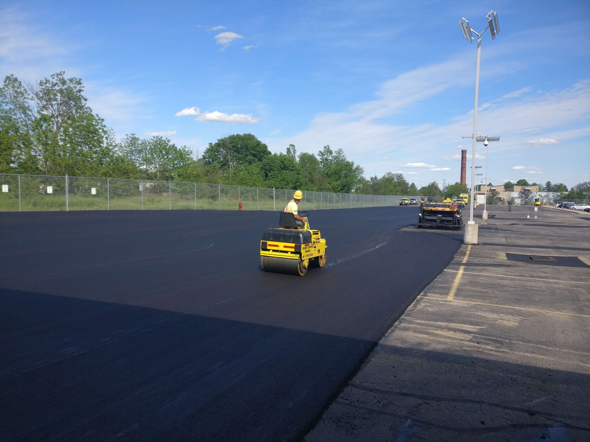 Construction employee fixing asphalt paving