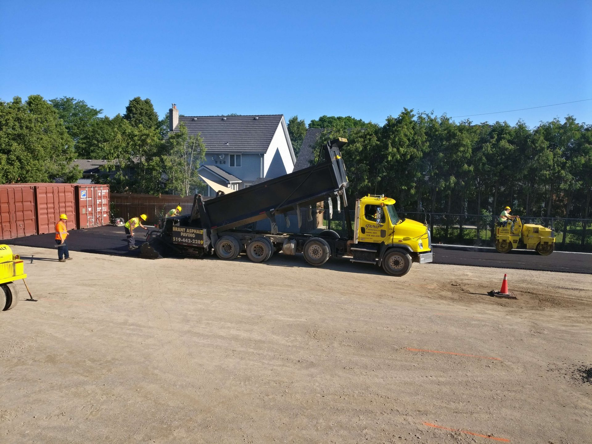 Dump truck pouring asphalt with Paris Construction workers