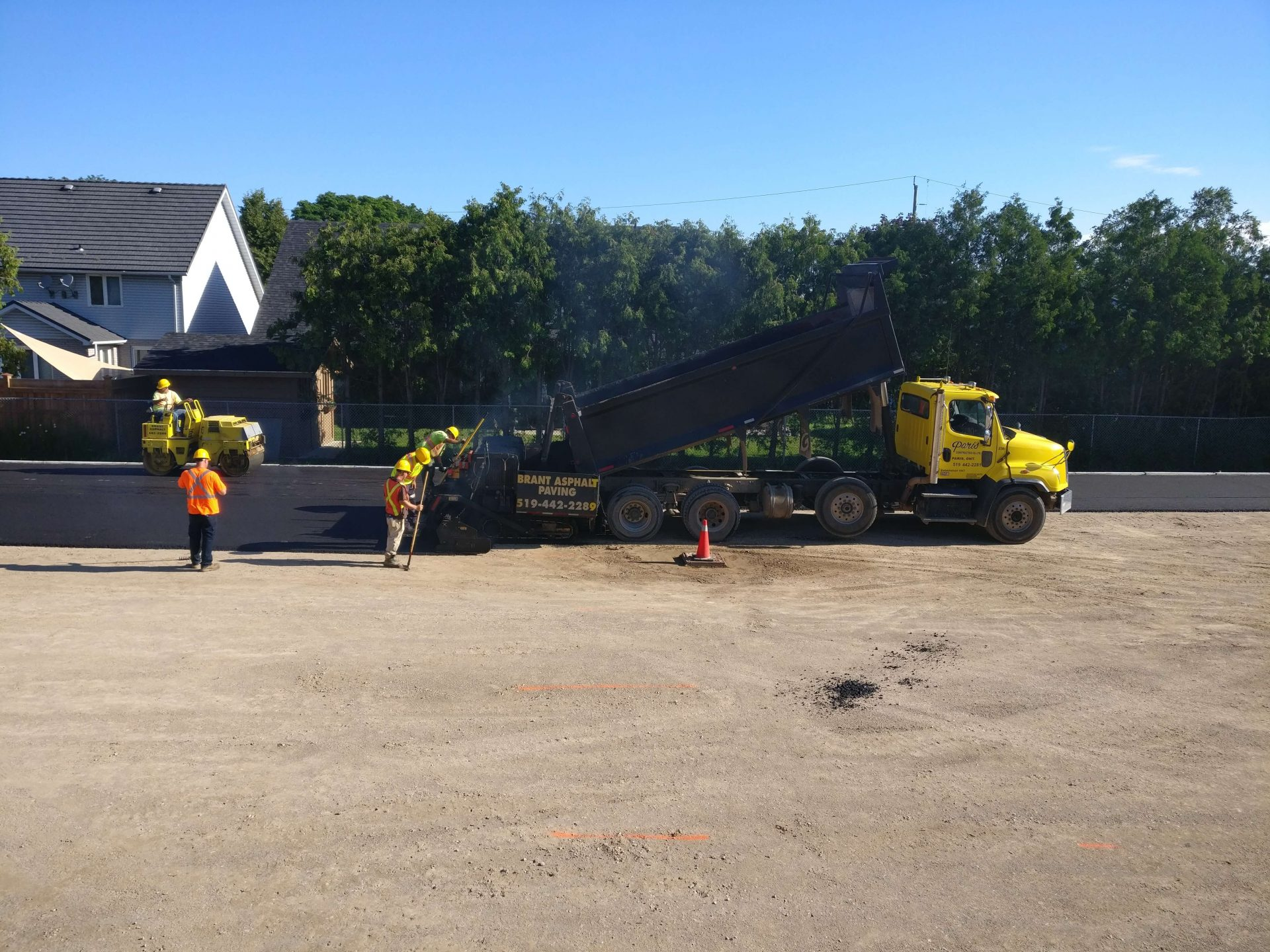 construction workers shovelling asphalt