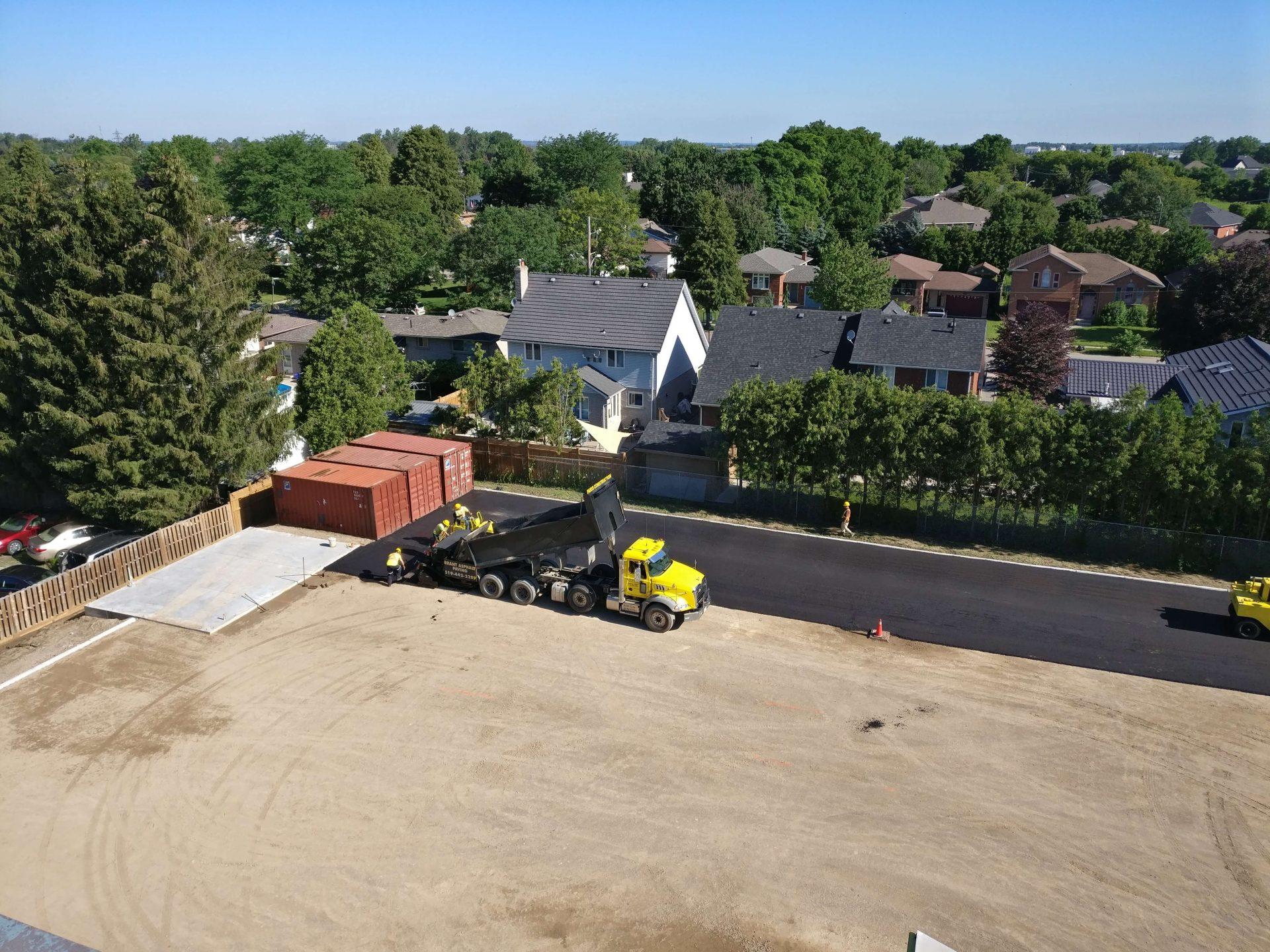 bare gravel parking lot with partial asphalt