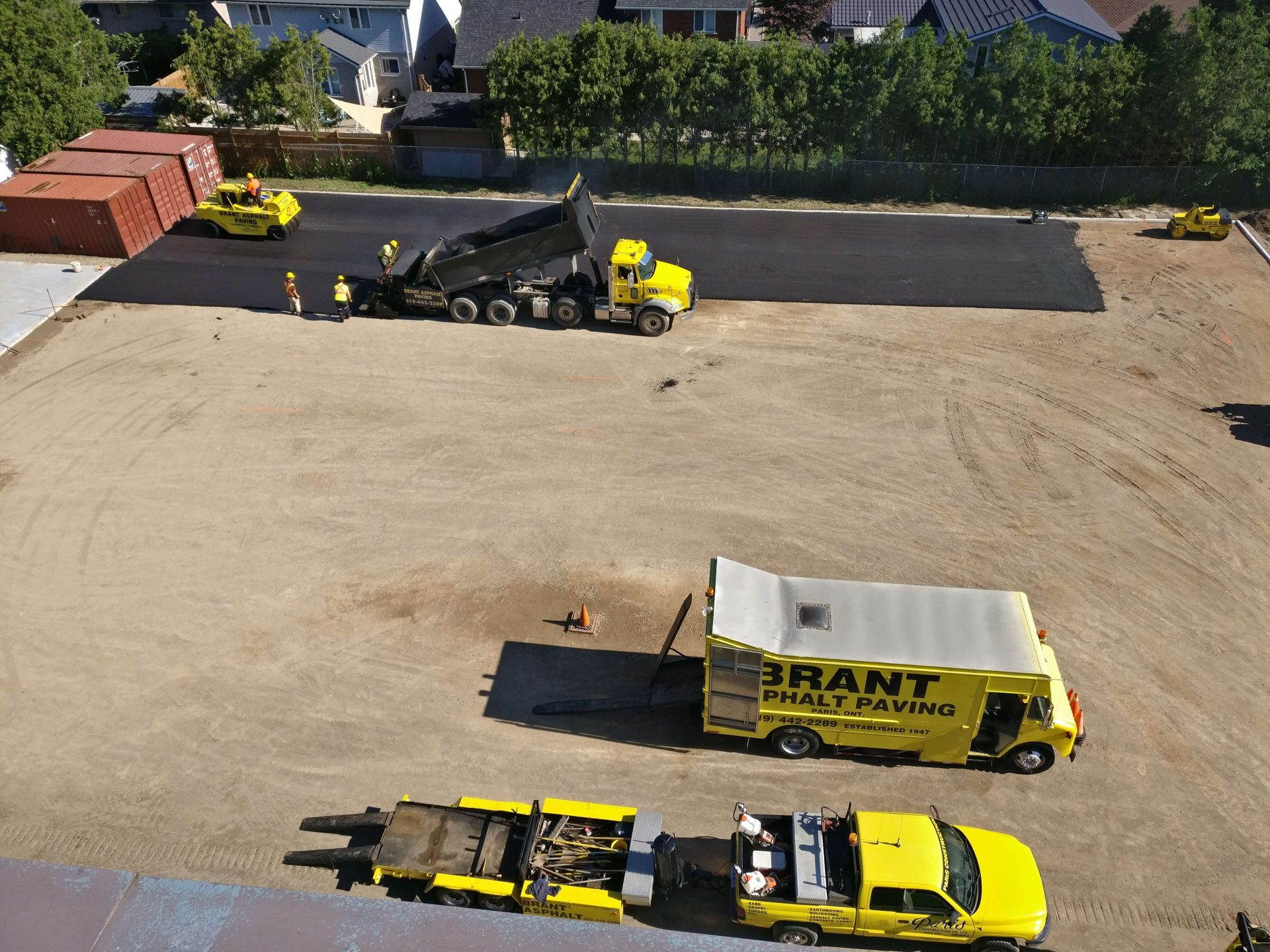 Asphalt paving with yellow trucks